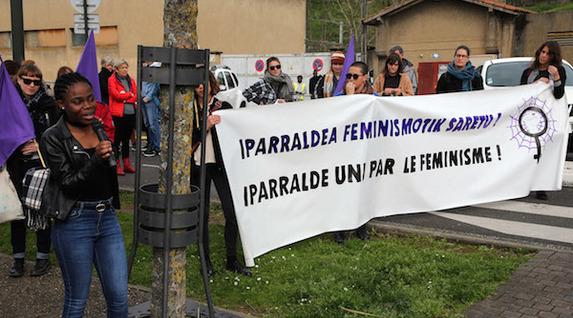 """""""Iparraldea feminismotik saretu"""" banderolaren ondoan, Clemence izeneko migranteak hartu zuen hitza. ©Bob EDME"""