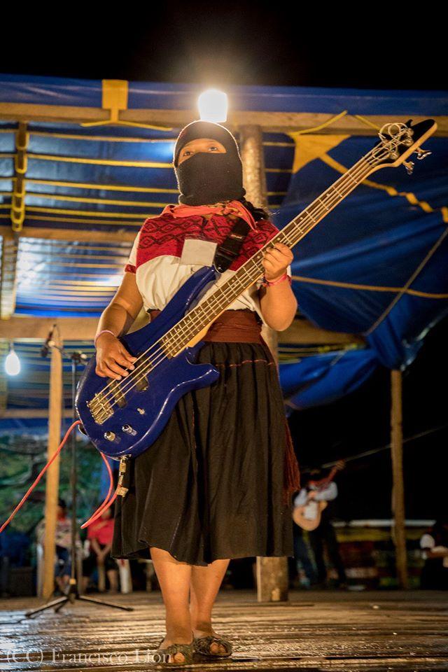 La imagen puede contener: una o varias personas, personas tocando instrumentos musicales, calzado, guitarra, niños y exterior
