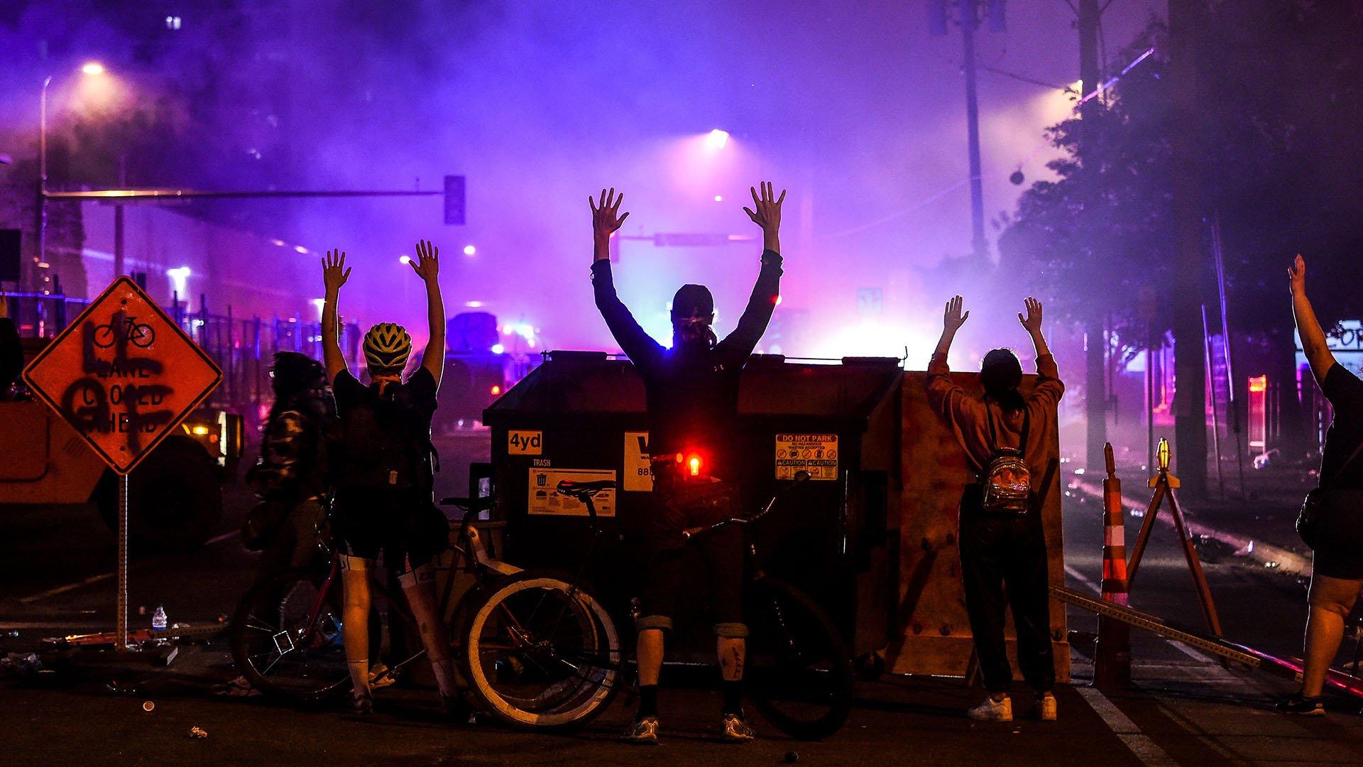 Manifestantes levantan sus brazos en Minneapolis, Minnesota (Chandan KHANNA / AFP)