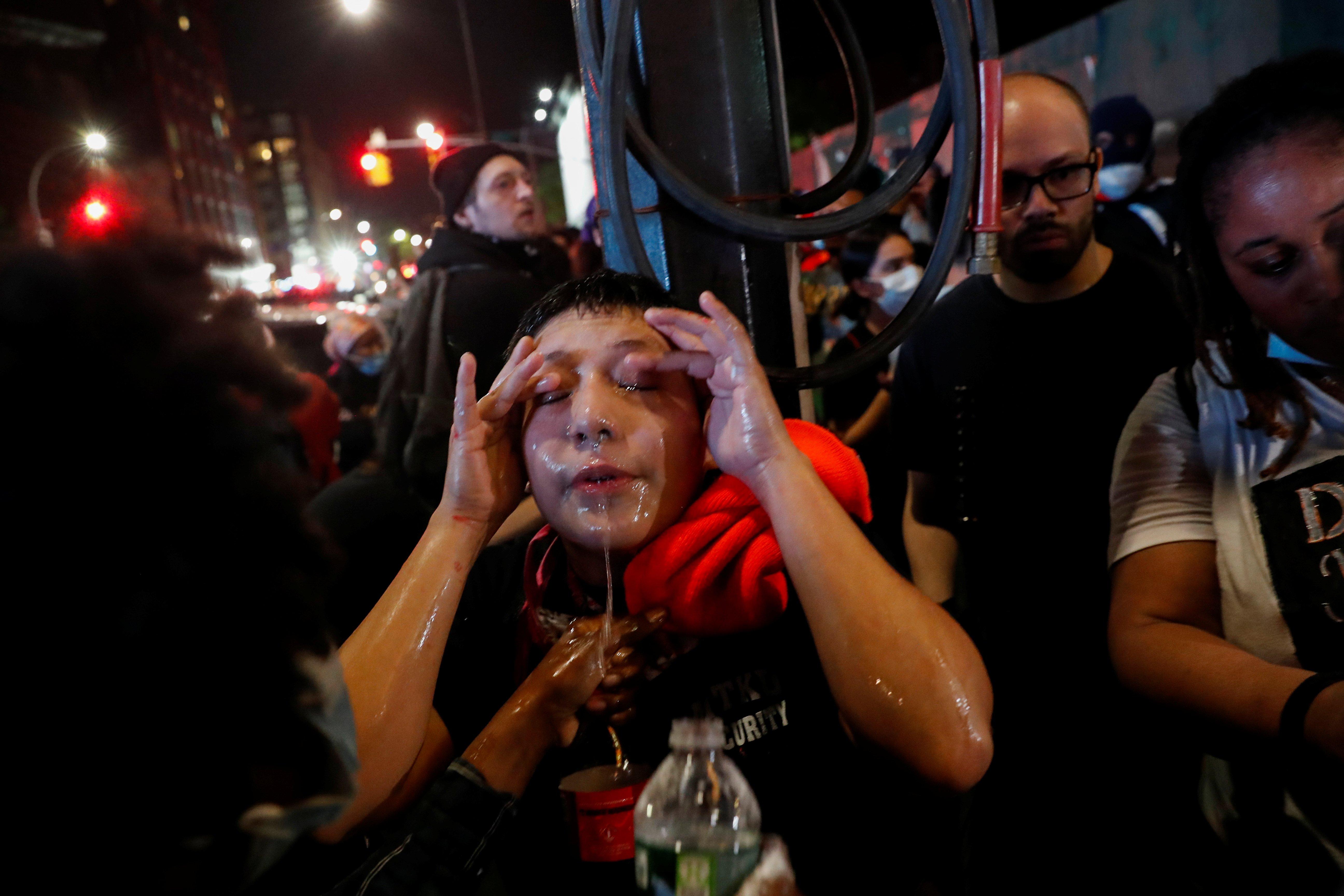 Una manifestante trata de reducir el efecto de los gases lacrimógenos con un lavado de cara en una manifestación que se realizó este viernes por la noche en Brooklyn, Nueva York (REUTERS/Shannon Stapleton)