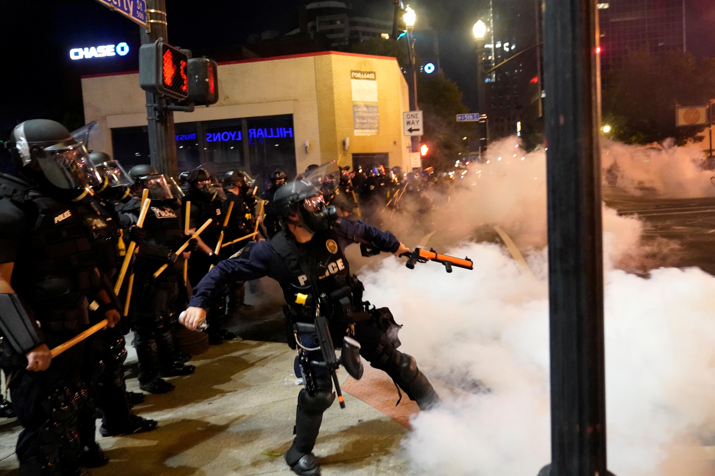 Un oficial lanza una bomba de gas en medio de los incidentes en Louisville, Kentucky (REUTERS/Bryan Woolston)