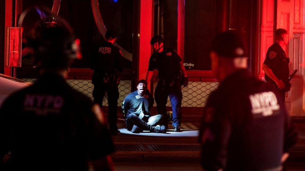 Agentes de la Policía de Nueva York detienten a un manifestante que saqueaba una tienda, en Manhattan.
