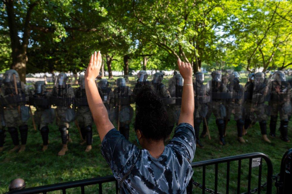 Una manifestante levanta los brazos frente a la Guardia Nacional a las afueras de la Casa Blanca. En un mensaje a la nación, el presidente Donald Trump amenazó con desplegar al Ejército en el resto del país si los gobernadores no frenan la violencia.