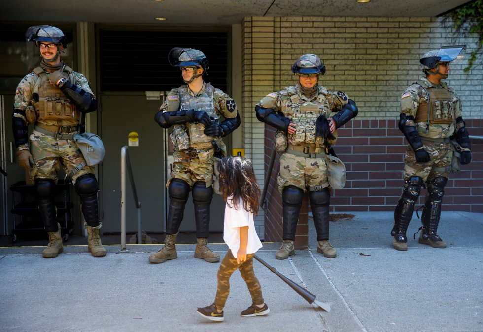 Un niña pasa frente a varios miembros de la Guardia Nacional, en Washington.