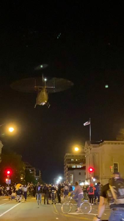 Un helicóptero vuela bajo sobre los manifestantes que se manifestaban contra la muerte en la custodia policial de George Floyd en Minneapolis, en Washington. TWITTER @MARIELCG3 /via REUTERS
