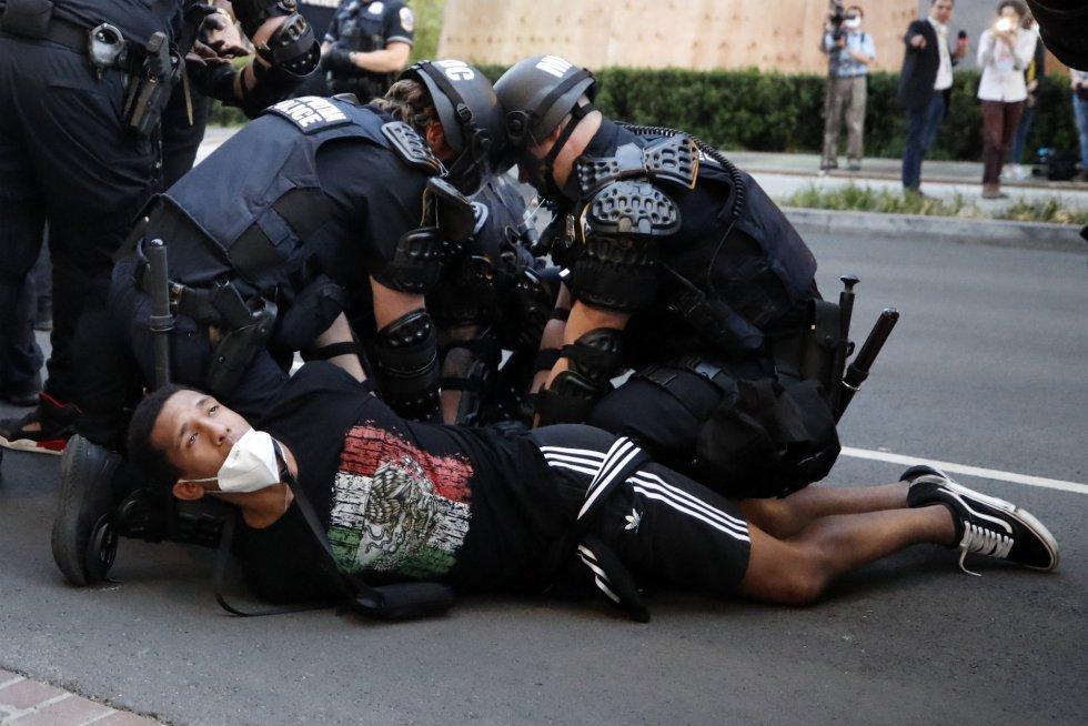 rnrnVarios agentes detienen a un manifestante en Washington.