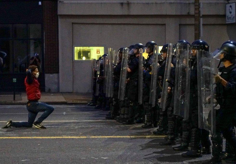 Un hombre se arrodilla frente a los agentes de policía, en una manifestación por la muerte de George Floyd, en San Luis.