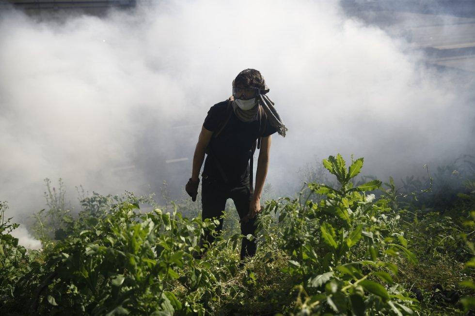 Un manifestante camina entre una nube de gas lacrimógeno durante las protestas de este lunes en Filadelfia.