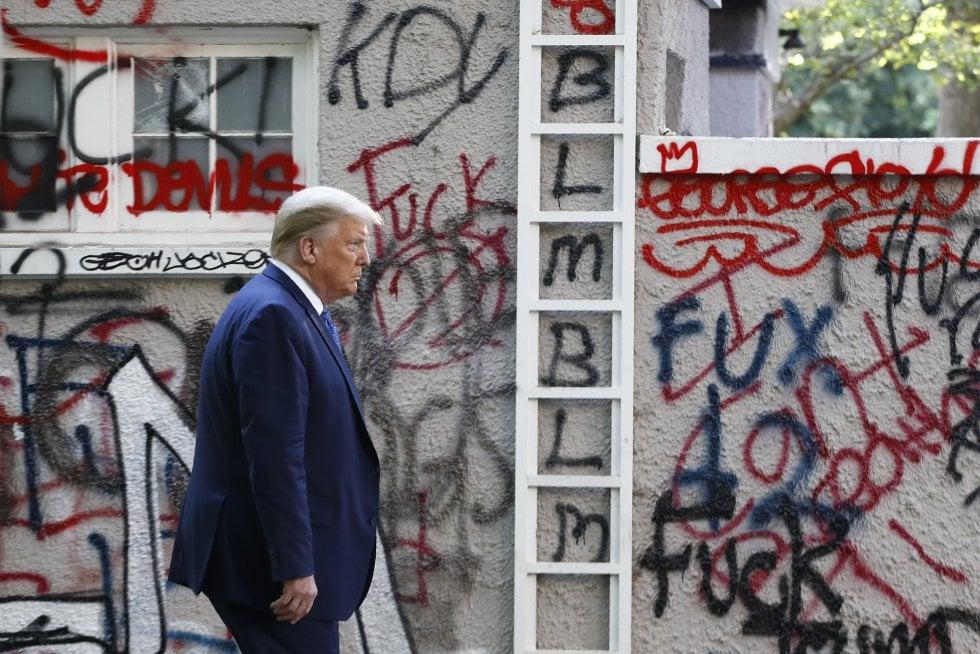 Trump camina frente a una pared cubierta de grafiti tras las protestas que continuaban el lunes a las afueras de la Casa Blanca. El presidente caminó hasta la iglesia de Saint John, cuyo sótano ardió en las revueltas del domingo, para fotografiarse a las puertas del templo sujetando una Biblia en la mano.