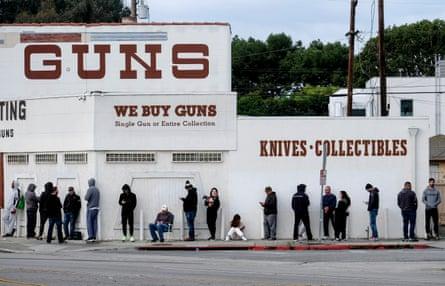 La gente espera en una fila para entrar a una tienda de armas en Culver City, California.