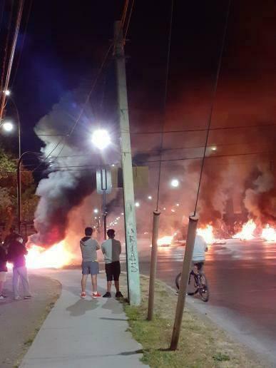La imagen puede contener: una o varias personas, personas de pie, fuego, noche y exterior