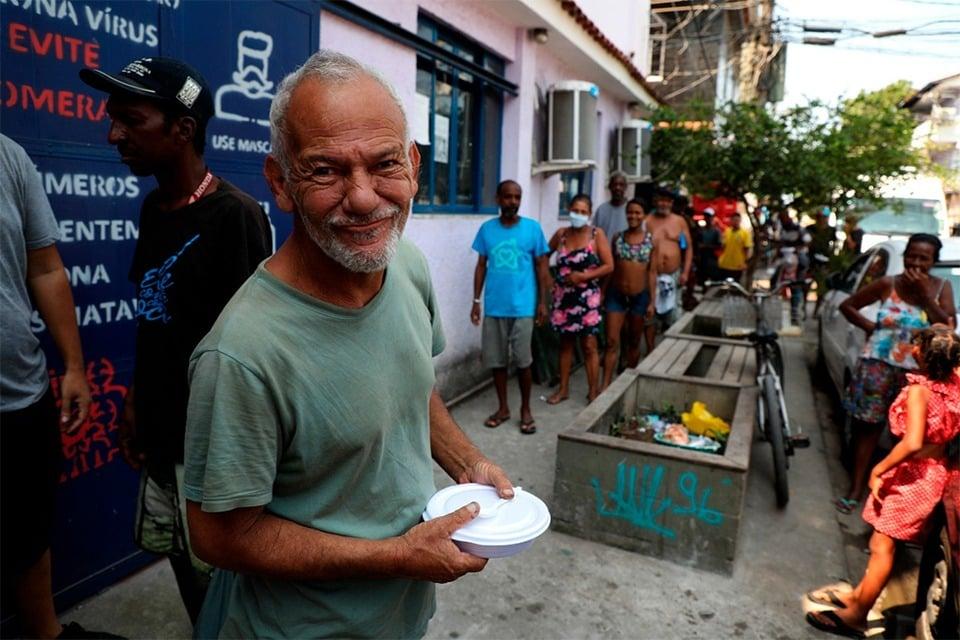 Habitantes de la favela da Maré hacen fila para recibir alimentos, en Rio de Janeiro.