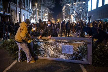 Demonstrators make barricades during clashes with police during a protest condemning the arrest of rap singer Pablo Hasél in Barcelona, Spain, Tuesday, Feb. 16, 2021. A 24-hour standoff between police and a rapper barricaded with dozens of his supporters in a university ended with the arrest of the artist, who has been sentenced to 9 months in prison for insulting the monarchy and praising terrorism. (AP Photo/Emilio Morenatti)