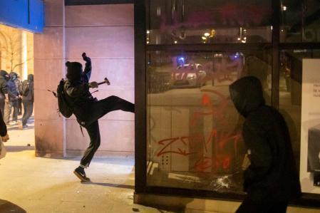 GRAF1066. GIRONA, 19/02/2021.- Un joven ataca un comercio durante los disturbios posteriores a la manifestación celebrada este viernes en Girona en protesta por la detención del rapero Pablo Hasél, acusado de delitos de enaltecimiento del terrorismo e injurias a la Corona. EFE/Toni Vilches