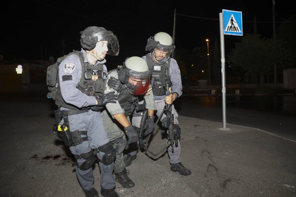 Un agente de policía israelí herido recibe ayuda durante los enfrentamientos en la mezquita. La Media Luna Roja habilitó un hospital de campaña para atender a los heridos, muchos por impactos de balas de goma y granadas de estruendo.