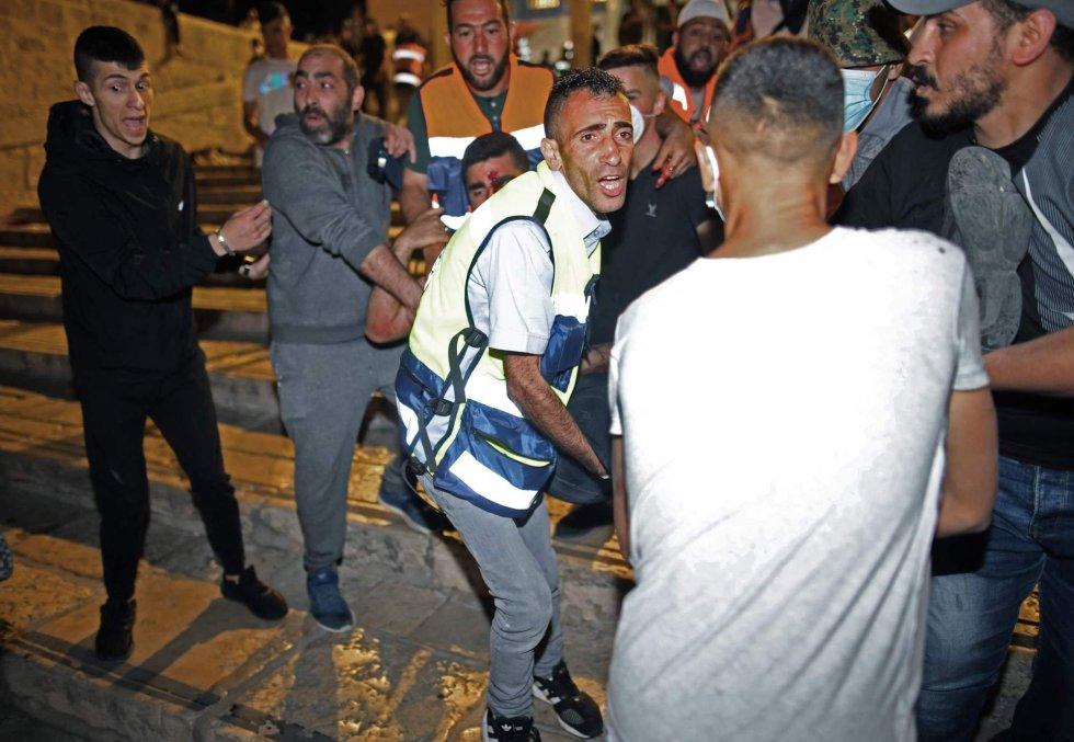 Al menos 205 palestinos y 17 policías israelíes han resultado heridos en la noche del viernes en choques con la policía en la mezquita de Al Aqsa de Jerusalén, tercer lugar sagrado del islam, según informó la Media Luna Roja palestina, que montó un hospital de campaña en la explanada del recinto. En la imagen, traslado de un herido palestino durante los enfrentamientos con las fuerzas de seguridad.