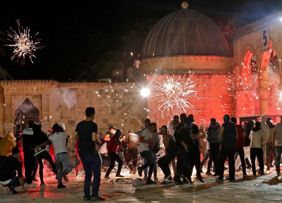 Decenas de miles de palestinos habían permanecido poco antes en pie en la explanada de la mezquita de Al Aqsa tras concluir el rezo en el último viernes de ramadán, en una movilización nacionalista con escasos precedentes en Jerusalén. En la imagen, un momento del choque con la policía israelí.