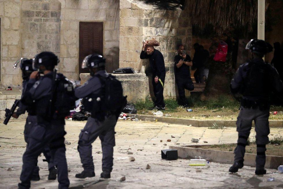 El barrio musulmán de la Ciudad Vieja quedó acordonado y las fuerzas israelíes cerraron el paso a través de la emblemática Puerta de Damasco. En la imagen, varios palestinos se ponen a cubierto durante los enfrentamientos con la policía israelí en el recinto que alberga la mezquita de Al-Aqsa.