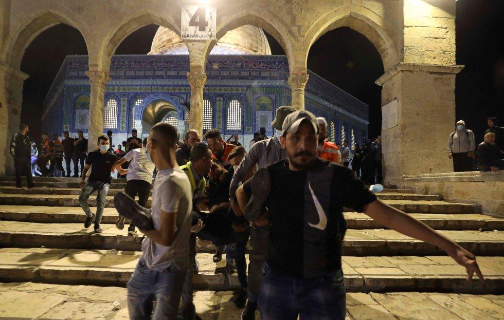 """Más de un centenar de palestinos habían resultado heridos el 23 de abril en anteriores enfrentamientos con la policía durante Ramadán ante la Puerta de Damasco de Jerusalén. En medio de una oleada de incidentes sucesivos, esa noche protestaban contra una marcha de cientos de ultraderechistas israelíes que se habían aproximado hasta el principal acceso al barrio musulmán de la Ciudad Vieja al grito de """"¡muerte a los árabes!"""". En la imagen, traslado de un herido palestino en la mezquita Al-Aqsa, en la noche de este viernes."""