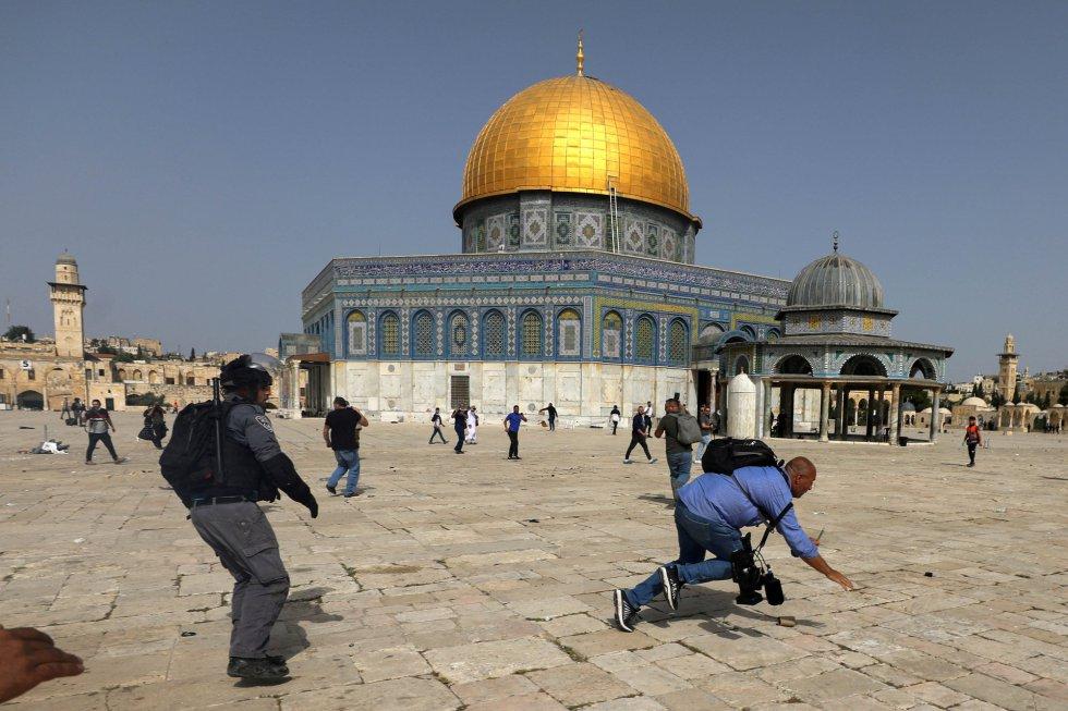 Un operador de cámara cae al suelo durante los enfrentamientos en el complejo que alberga la mezquita Al Aqsa, este lunes.