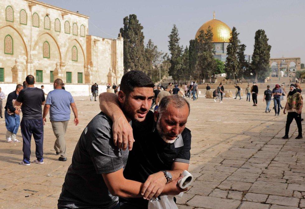 """Un palestino ayuda a un manifestante herido en medio de los enfrentamientos en la mezquita Al Aqsa, este lunes. Los enfrentamientos con agentes de la policía israelí comenzaron por la mañana y acabaron con """"215 heridos"""", según informó el servicio de emergencias Media Luna Roja, que concretó que más de 153 tuvieron que ser evacuados a hospitales de la ciudad o trasladados a su clínica de campaña."""