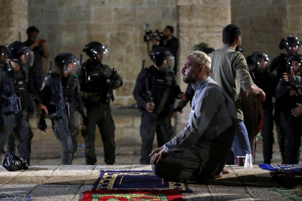 La violencia también ha saltado en Cisjordania ocupada y este viernes dos palestinos murieron por disparos israelíes tras intentar atacar con armas de fuego a policías y soldados israelíes en un puesto de control. Se trataba del segundo ataque con arma de fuego de la semana, tras el del pasado domingo en el que murió un joven israelí palestino. En la imagen, un palestino reza durante los enfrentamientos en la mezquita de Al-Aqsa.