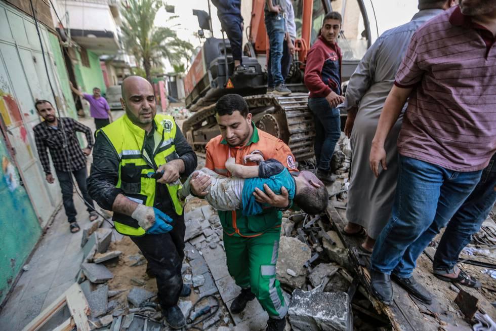 Personal sanitario traslada el cuerpo de un niño rescatado entre los escombros de un edificio en Gaza. Los equipos de rescate gazatíes han buscado cuerpos y supervivientes entre los escombros durante toda la mañana.
