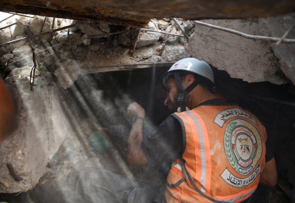 """Personal de rescate trabaja entre los escombros de un edifico derrumbado durante un bombardeo en Gaza, este domingo. La misma fuente castrense hizo constar que las dependencias de la milicia islamista """"se hallaban junto a un jardín de infancia"""". """"Esto demuestra que Hamás pone en peligro a los civiles al situar instalaciones militares en zonas densamente pobladas""""."""