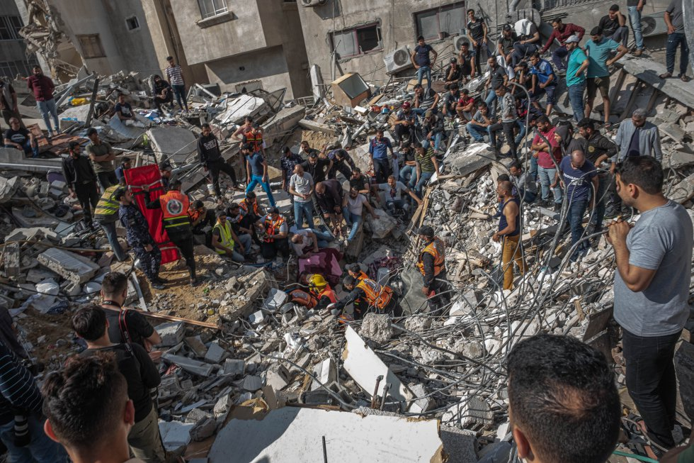 Personal de emergencias y voluntarios buscan supervivientes en un edificio destruido durante un bombardeo en Gaza, este domingo. La operación, que de acuerdo con un portavoz del Ejército israelí iba dirigida contra la sede del centro de inteligencia de Hamás en el norte de la Franja, ha arrasado tres edificios.