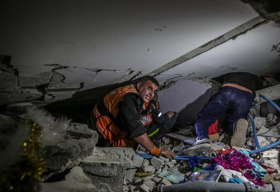 Personal de rescate busca supervivientes entre los escombros de un edificio en Gaza. Al menos 10 miembros de una misma familia fallecieron el sábado en el campo de refugiados de Al Shati, en una de las ofensivas de la aviación israelí, al desplomarse el inmueble en el que vivían.