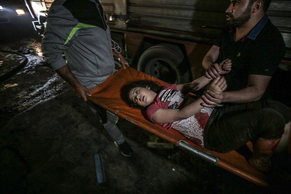 Una niña es trasladada tras ser recatada en Gaza, este domingo. El sábado por la noche, una clínica de Médicos sin Fronteras en la ciudad de Gaza también resultó dañada por un bombardeo de la aviación israelí, dejando una sala de esterilización inutilizable.