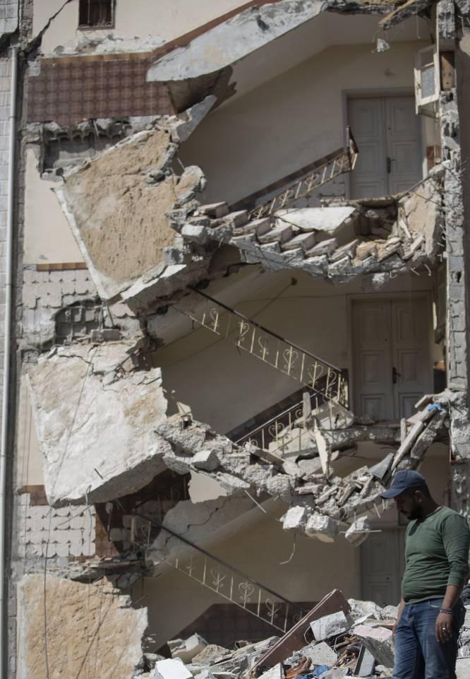 Un hombre busca supervivientes entre los escombros de un edificio en Gaza. Amnistía Internacional y otras organizaciones humanitarias han pedido al Tribunal Penal Internacional, que investiga los presuntos crímenes cometidos por el Ejército israelí y las milicias gazatíes a partir de 2014, que incorpore los últimos casos de bombardeos masivos.