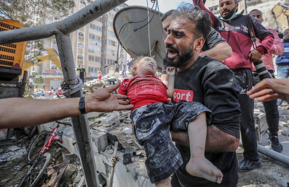 """Un palestino lleva el cuerpo sin vida de su hija tras rescatarlo de entre los escombros de un edificio destruido en un ataque aéreo en la ciudad de Gaza. El secretario general de la ONU, António Guterres, ha advertido a los bandos en conflicto que """"los ataques indiscriminados contra civiles violan las leyes internacionales"""""""