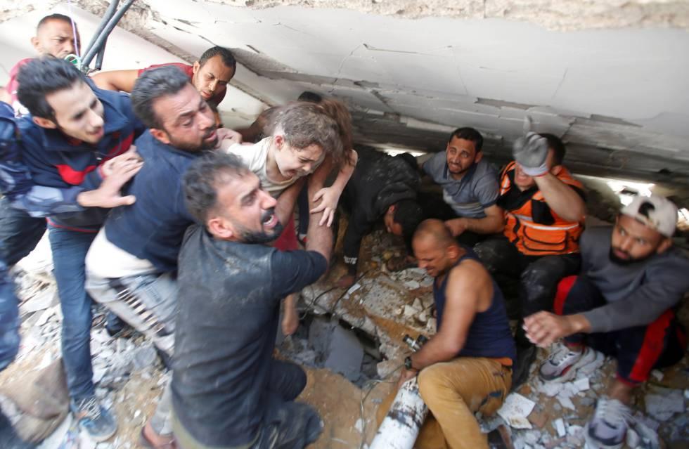 Palestinos rescatan a una niña entre los escombros de un edificio en Gaza, este domingo. El Ejército israelí ha incrementado los bombardeos sobre la franja de Gaza, con más de un millar de operaciones aéreas, mientras las milicias de Hamás han redoblado el disparo de cohetes tras cerca de tres millares de lanzamientos. Desde la guerra de 2014, que se prolongó durante dos meses, ambas partes no se habían enfrentado con tanta intensidad.