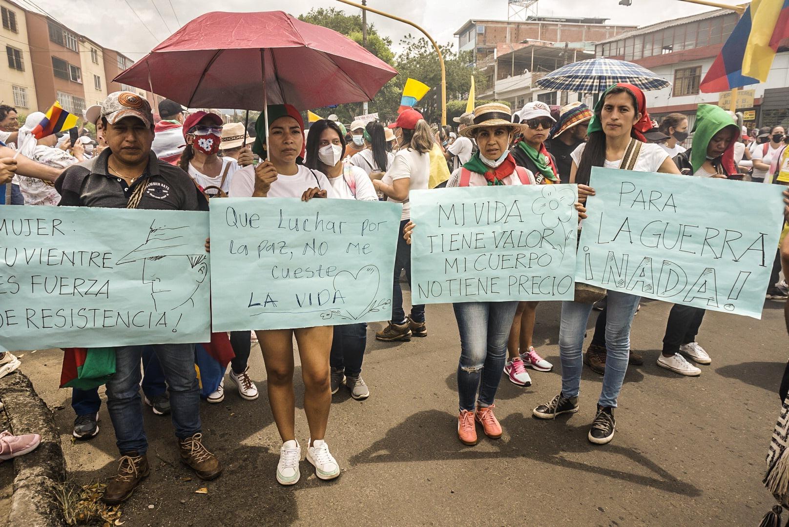 """Puede ser una imagen de 7 personas, personas caminando, personas de pie, multitud, al aire libre y texto que dice """"MUTER VIENTRE S FUERZA E RESISTENCIA Que Luchar por Lapaz,nOM Me la Pz, NO cueste LA VIDA MIVIDA PARA TIENE VALOR MICUERPO LAGUERRA NOTIENE PRECIO NADA!"""""""