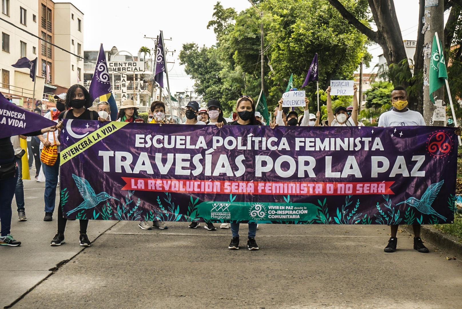"""Puede ser una imagen de 2 personas, personas de pie, al aire libre y texto que dice """"MERCI VENCERÁ A VIDA! EIR FUSTICIA PAZ MAS VIOLENCIA #VENCERAL LA VIDA ESCUELA POLÍTICA FEMINISTA TRAVESÍAS POR LA PAZ LAREVOLUCIÓN SERÁ FEMINISTA 0 no SERÁ VIVIREN O-INSPIRACIÓN COMUNITARIA"""""""