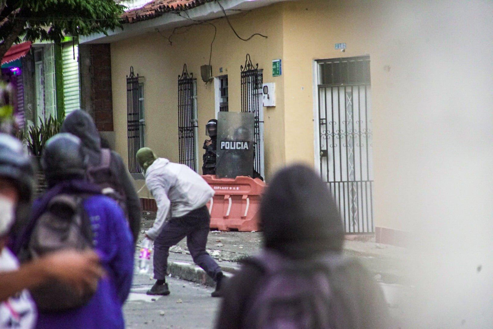 """Puede ser una imagen de una o varias personas, personas de pie, calle y texto que dice """"POLICIA"""""""