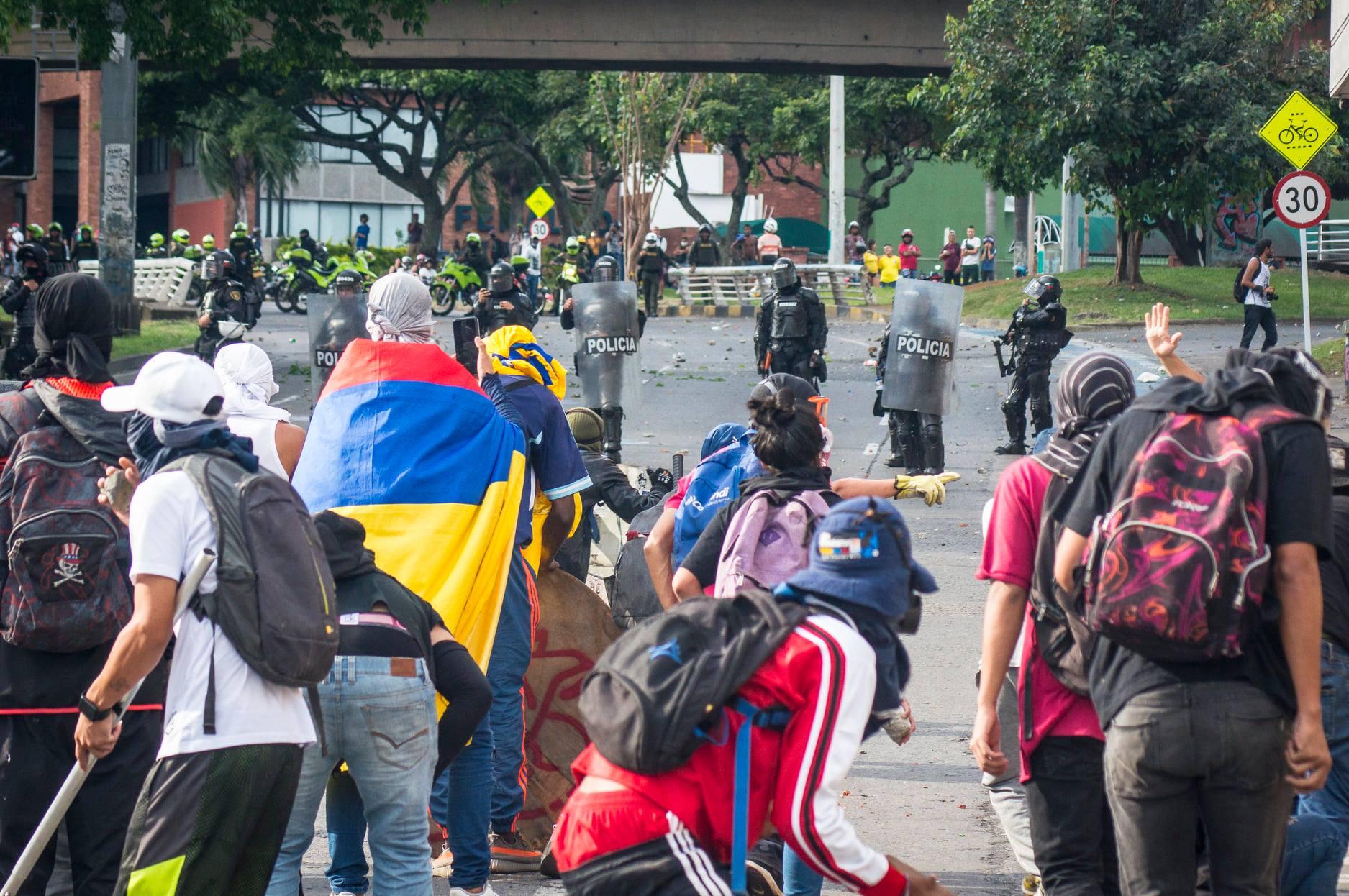 """Puede ser una imagen de una o varias personas, personas de pie, personas caminando, moto, calle, multitud, carretera y texto que dice """"50 POLICIA POLICIA ICIA POLI"""""""