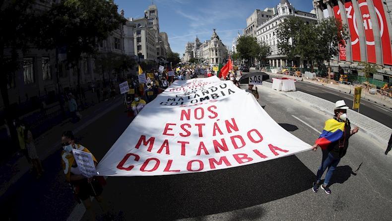"""En la movilización se desplegó una amplia pancarta que señala """"Nos están matando"""" y una larga bandera colombiana con el lema """"Colombia por la paz y la unidad""""."""